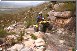 A quad bike grinds its way up the mountain trail